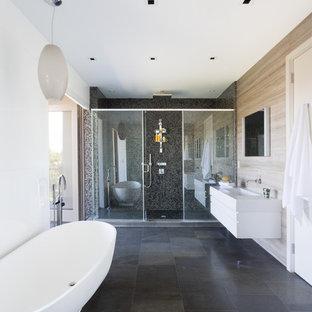 Ejemplo de cuarto de baño principal, contemporáneo, grande, con bañera exenta, armarios con paneles lisos, puertas de armario blancas, ducha empotrada, paredes blancas, lavabo integrado, encimera de acrílico y baldosas y/o azulejos de pizarra