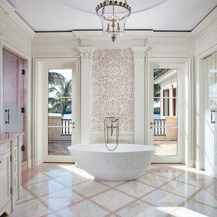 На фото: главная ванная комната в средиземноморском стиле с фасадами с утопленной филенкой, белыми фасадами, отдельно стоящей ванной, белой плиткой, белыми стенами, монолитной раковиной, разноцветным полом, розовой столешницей, мраморной плиткой, полом из керамогранита и мраморной столешницей с
