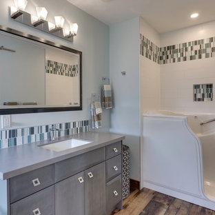Esempio di una stanza da bagno padronale moderna di medie dimensioni con ante lisce, ante grigie, vasca freestanding, piastrelle blu, lastra di vetro, pareti grigie, parquet chiaro, lavabo sottopiano, top in legno, pavimento marrone e top grigio