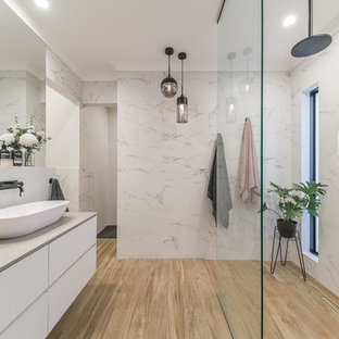 Large contemporary bathroom in Perth with white cabinets, an open shower, ceramic tile, ceramic floors, a vessel sink, solid surface benchtops, an open shower, flat-panel cabinets, white tile, white walls, beige floor and beige benchtops.