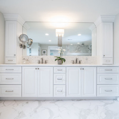 Example of a large mountain style master white tile and stone tile marble floor and multicolored floor drop-in bathtub design in DC Metro with raised-panel cabinets, white cabinets, gray walls, an undermount sink, marble countertops, a two-piece toilet and white countertops