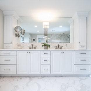 Foto på ett stort rustikt vit en-suite badrum, med luckor med upphöjd panel, vita skåp, ett platsbyggt badkar, vit kakel, stenkakel, grå väggar, marmorgolv, ett undermonterad handfat, marmorbänkskiva, en toalettstol med separat cisternkåpa och flerfärgat golv