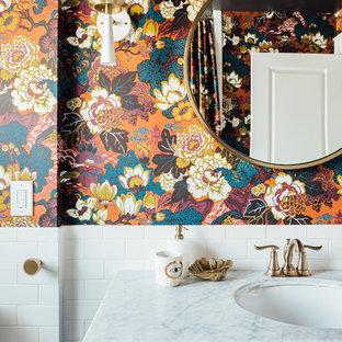 Modelo de cuarto de baño con ducha, ecléctico, de tamaño medio, con armarios estilo shaker, puertas de armario azules, bañera encastrada, combinación de ducha y bañera, sanitario de una pieza, baldosas y/o azulejos blancos, baldosas y/o azulejos de cerámica, paredes multicolor, suelo de baldosas de porcelana, lavabo integrado, encimera de mármol, suelo blanco, ducha con cortina y encimeras blancas