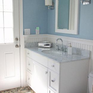 Ispirazione per una piccola stanza da bagno con doccia costiera con ante in stile shaker, ante bianche, WC a due pezzi, piastrelle di ciottoli, pareti blu, pavimento con piastrelle di ciottoli, lavabo sottopiano e top in marmo
