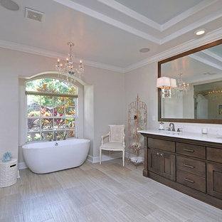 Idee per una stanza da bagno padronale shabby-chic style di medie dimensioni con lavabo a bacinella, consolle stile comò, ante grigie, top in quarzo composito, doccia a filo pavimento, WC a due pezzi, piastrelle beige, piastrelle di vetro, pareti grigie, pavimento in gres porcellanato e vasca freestanding