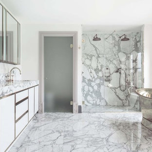 This is an example of a classic ensuite bathroom in Oxfordshire with flat-panel cabinets, white cabinets, a freestanding bath, a built-in shower, grey tiles, white walls, a submerged sink, grey floors, a hinged door and grey worktops.