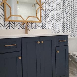 Diseño de cuarto de baño principal, costero, de tamaño medio, con armarios estilo shaker, puertas de armario grises, baldosas y/o azulejos blancos, paredes amarillas, suelo de madera pintada, lavabo bajoencimera, encimera de cuarcita y suelo blanco