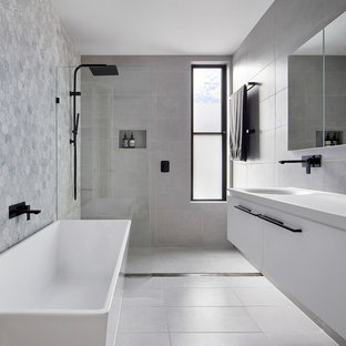 Small contemporary master bathroom in Melbourne with a freestanding tub, an open shower, gray tile, marble, porcelain floors, an integrated sink, solid surface benchtops, grey floor, an open shower, white benchtops, flat-panel cabinets, white cabinets and grey walls.