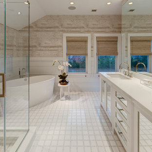 Freestanding bathtub - mid-sized contemporary master white tile vinyl floor freestanding bathtub idea in New York with recessed-panel cabinets, white cabinets, white walls and an undermount sink
