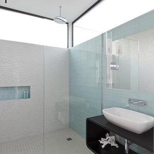 ヒューストンのモダンスタイルのおしゃれな浴室 (ガラスタイル、木製洗面台、段差なし、青いタイル、磁器タイルの床、白い壁、グレーの床、黒い洗面カウンター) の写真