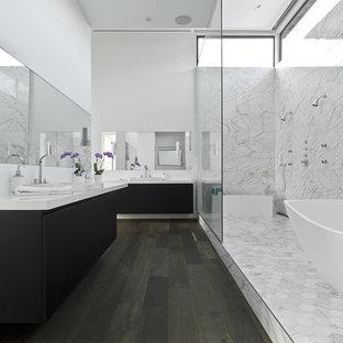 Ispirazione per una stanza da bagno design con lavabo da incasso, ante lisce, ante nere, vasca freestanding, doccia doppia e piastrelle bianche