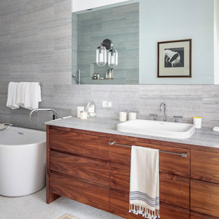 Bathroom - mid-sized contemporary master white tile and mosaic tile bathroom idea in New York with flat-panel cabinets, white cabinets, a one-piece toilet, gray walls, an undermount sink, marble countertops, a hinged shower door and white countertops