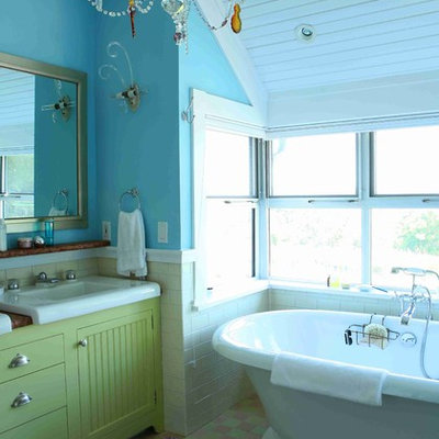 Mid-sized eclectic master mosaic tile floor freestanding bathtub photo in New York with beaded inset cabinets, green cabinets, a one-piece toilet, blue walls, an integrated sink and solid surface countertops