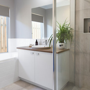 Medium sized coastal family bathroom in Brisbane with flat-panel cabinets, white cabinets, a corner shower, grey tiles, ceramic tiles, grey walls, ceramic flooring, a built-in sink, laminate worktops, grey floors, a hinged door and brown worktops.