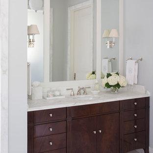 Esempio di un'ampia stanza da bagno padronale con consolle stile comò, ante in legno bruno, piastrelle bianche, pareti blu, lavabo da incasso e top in saponaria