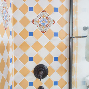 This is an example of a large mediterranean ensuite bathroom in Other with raised-panel cabinets, light wood cabinets, a submerged bath, an alcove shower, a two-piece toilet, blue tiles, white tiles, white walls, terracotta flooring, a submerged sink, tiled worktops, brown floors and a sliding door.