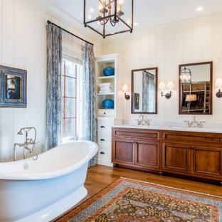 Inredning av ett lantligt stort vit vitt en-suite badrum, med luckor med profilerade fronter, skåp i mörkt trä, ett fristående badkar, vita väggar, mellanmörkt trägolv, ett undermonterad handfat, marmorbänkskiva och brunt golv