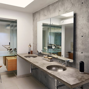 This is an example of a mid-sized industrial master bathroom in Other with open cabinets, a two-piece toilet, gray tile, cement tile, grey walls, ceramic floors, an undermount sink, concrete benchtops and beige floor.