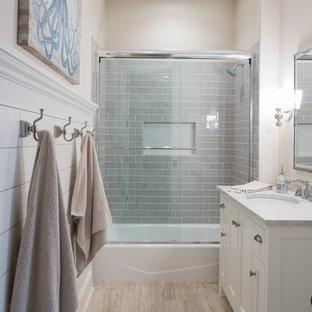 Foto di una stanza da bagno con doccia stile marinaro con ante con riquadro incassato, ante bianche, vasca ad alcova, vasca/doccia, piastrelle grigie, piastrelle di vetro, pareti beige, lavabo sottopiano, pavimento beige e porta doccia scorrevole