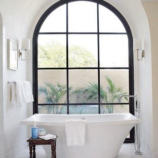 Idée de décoration pour une salle de bain principale méditerranéenne avec une baignoire indépendante et un mur blanc.