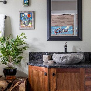 Modelo de cuarto de baño principal, actual, grande, con armarios estilo shaker, puertas de armario de madera oscura, suelo de mármol, lavabo sobreencimera, encimera de granito, suelo beige, encimeras negras y paredes grises