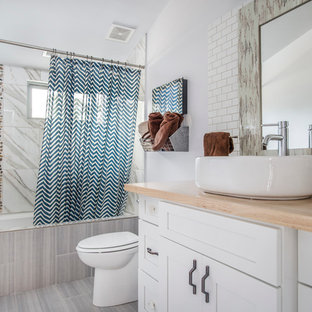 Idee per una stanza da bagno country di medie dimensioni con ante in stile shaker, ante bianche, vasca/doccia, pareti bianche, pavimento in laminato, lavabo a bacinella, top in legno, vasca ad alcova, piastrelle bianche e doccia con tenda
