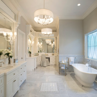 Large transitional master gray tile and mosaic tile marble floor freestanding bathtub photo in Houston with white cabinets, marble countertops, gray walls and shaker cabinets