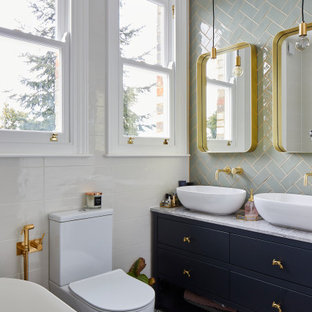 Photo of a medium sized traditional ensuite bathroom in London with flat-panel cabinets, blue cabinets, a freestanding bath, a one-piece toilet, green tiles, white tiles, a vessel sink, multi-coloured floors, grey worktops, double sinks and a built in vanity unit.
