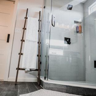 Foto de cuarto de baño principal, campestre, de tamaño medio, con armarios estilo shaker, puertas de armario grises, ducha esquinera, paredes blancas, suelo vinílico, lavabo bajoencimera, encimera de cuarcita, suelo negro, ducha con puerta con bisagras y encimeras blancas