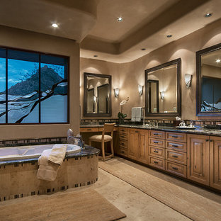 Photo of a large ensuite bathroom in Phoenix with a submerged sink, raised-panel cabinets, medium wood cabinets, a built-in shower, beige walls, limestone flooring, granite worktops, matchstick tiles, beige tiles, brown tiles, a built-in bath and beige floors.