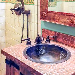 Modelo de cuarto de baño principal, de estilo americano, de tamaño medio, con armarios tipo mueble, puertas de armario con efecto envejecido, ducha empotrada, baldosas y/o azulejos multicolor, baldosas y/o azulejos blancos, baldosas y/o azulejos en mosaico, paredes azules, suelo de baldosas de terracota, lavabo encastrado, encimera de cobre, suelo marrón y ducha con puerta con bisagras