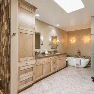 フェニックスの大きいトランジショナルスタイルのおしゃれなマスターバスルーム (シェーカースタイル扉のキャビネット、淡色木目調キャビネット、茶色いタイル、ガラスタイル、ベージュの壁、トラバーチンの床、アンダーカウンター洗面器、クオーツストーンの洗面台) の写真