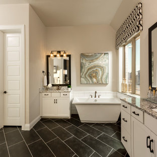 Bathroom - huge southwestern master white tile and subway tile porcelain tile, black floor and double-sink bathroom idea in Houston with shaker cabinets, white cabinets, beige walls, an undermount sink, granite countertops, a hinged shower door, gray countertops and a built-in vanity