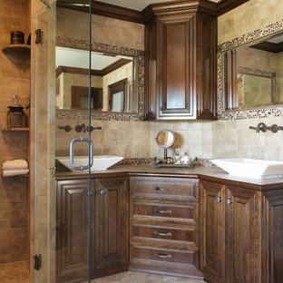 Inspiration for a mid-sized eclectic master beige tile and stone slab porcelain tile bathroom remodel in Newark with a vessel sink, furniture-like cabinets, dark wood cabinets, tile countertops, a one-piece toilet and beige walls
