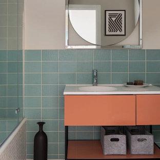 Immagine di una stanza da bagno padronale design di medie dimensioni con ante lisce, ante arancioni, vasca sottopiano, vasca/doccia, WC sospeso, piastrelle blu, piastrelle in ceramica, pareti beige, pavimento in cementine, lavabo a consolle, top in superficie solida, pavimento arancione, doccia con tenda e top bianco