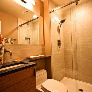 Modern inredning av ett litet badrum med dusch, med släta luckor, skåp i mellenmörkt trä, en dusch i en alkov, en toalettstol med hel cisternkåpa, beige väggar, ett undermonterad handfat och bänkskiva i akrylsten