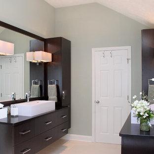 Идея дизайна: главная ванная комната среднего размера в стиле модернизм с плоскими фасадами, коричневыми фасадами, отдельно стоящей ванной, открытым душем, унитазом-моноблоком, зеленой плиткой, плиткой из листового стекла, зелеными стенами, полом из керамогранита, настольной раковиной, столешницей из талькохлорита, серым полом и душем с распашными дверями