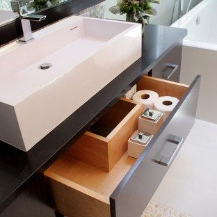 Удачное сочетание для дизайна помещения: главная ванная комната среднего размера в стиле модернизм с плоскими фасадами, коричневыми фасадами, отдельно стоящей ванной, открытым душем, унитазом-моноблоком, зеленой плиткой, плиткой из листового стекла, зелеными стенами, полом из керамогранита, настольной раковиной, столешницей из талькохлорита, серым полом и душем с распашными дверями - самое интересное для вас