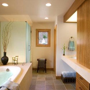 Modelo de cuarto de baño principal, de estilo zen, de tamaño medio, con armarios con paneles lisos, puertas de armario de madera clara, bañera encastrada, ducha esquinera, baldosas y/o azulejos beige, baldosas y/o azulejos de cerámica, paredes blancas, suelo de pizarra, lavabo bajoencimera y encimera de esteatita