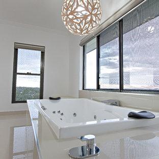Immagine di un'ampia stanza da bagno padronale minimalista con ante bianche, vasca idromassaggio, pareti bianche, pavimento in gres porcellanato, top piastrellato, pavimento beige e top bianco