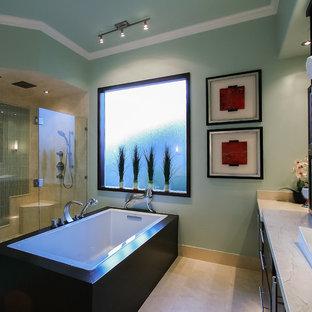 Immagine di una stanza da bagno padronale minimalista di medie dimensioni con lavabo a bacinella, ante di vetro, ante in legno bruno, top in marmo, vasca freestanding, doccia a filo pavimento, WC a due pezzi, piastrelle beige, pareti verdi e pavimento in travertino