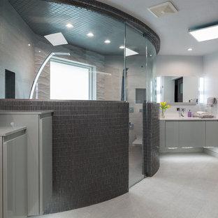 Ispirazione per una stanza da bagno padronale design di medie dimensioni con ante lisce, ante grigie, vasca da incasso, doccia doppia, WC a due pezzi, piastrelle nere, piastrelle grigie, piastrelle a mosaico, pareti grigie, pavimento in gres porcellanato, lavabo integrato e top in superficie solida