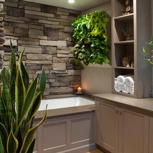 Modelo de cuarto de baño principal, asiático, de tamaño medio, con armarios con paneles empotrados, puertas de armario beige, bañera encastrada sin remate, paredes grises, suelo de madera clara, lavabo sobreencimera y encimera de cuarzo compacto