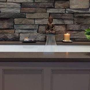 Immagine di una stanza da bagno padronale etnica di medie dimensioni con ante con riquadro incassato, ante beige, vasca sottopiano, pareti grigie, lavabo a bacinella e top in quarzo composito