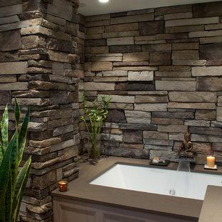 Foto di una stanza da bagno padronale etnica di medie dimensioni con ante con riquadro incassato, ante beige, vasca sottopiano, pareti grigie, lavabo a bacinella e top in quarzo composito