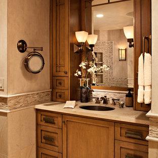 オレンジカウンティの中くらいのトランジショナルスタイルのおしゃれなマスターバスルーム (シェーカースタイル扉のキャビネット、中間色木目調キャビネット、ドロップイン型浴槽、コーナー設置型シャワー、分離型トイレ、ベージュのタイル、石タイル、ベージュの壁、ライムストーンの床、アンダーカウンター洗面器、ライムストーンの洗面台) の写真