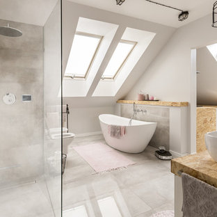 Contemporary master bathroom in New York with a freestanding tub, a corner shower, white walls, a vessel sink, grey floor, beige benchtops, a bidet and an open shower.
