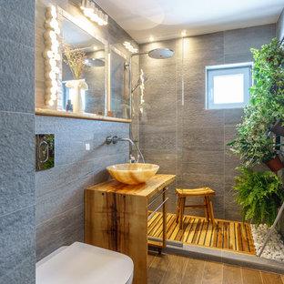 Bild på ett litet tropiskt badrum med dusch, med vita skåp, en dusch i en alkov, en vägghängd toalettstol, grå kakel, keramikplattor, grå väggar, klinkergolv i keramik, ett fristående handfat och träbänkskiva