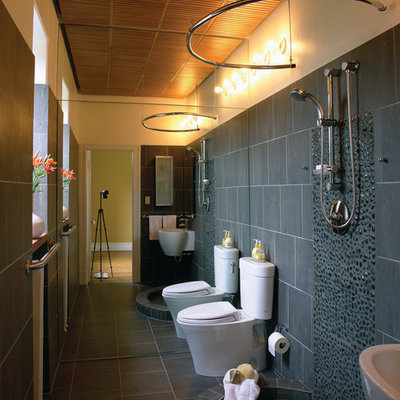 Example of a trendy gray tile and pebble tile bathroom design in DC Metro with a wall-mount sink and a two-piece toilet