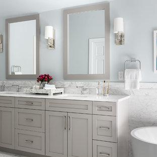 Bild på ett mellanstort vintage vit vitt en-suite badrum, med skåp i shakerstil, grå skåp, ett fristående badkar, vit kakel, marmorkakel, grå väggar, marmorgolv, ett undermonterad handfat, bänkskiva i kvarts och vitt golv
